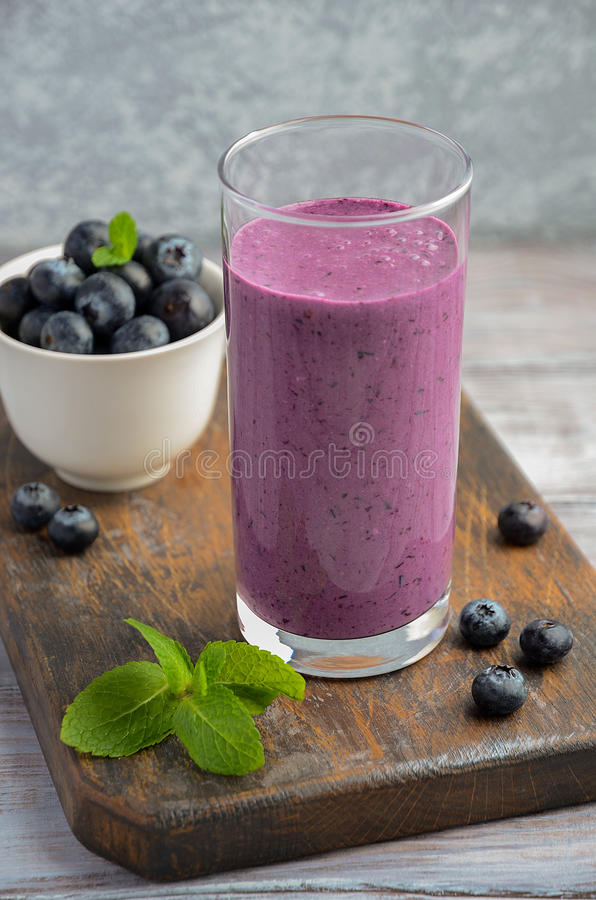 Blueberry and banana smoothie with oatmeal on the rustic wooden table. Selective focus, copy space royalty free stock image
