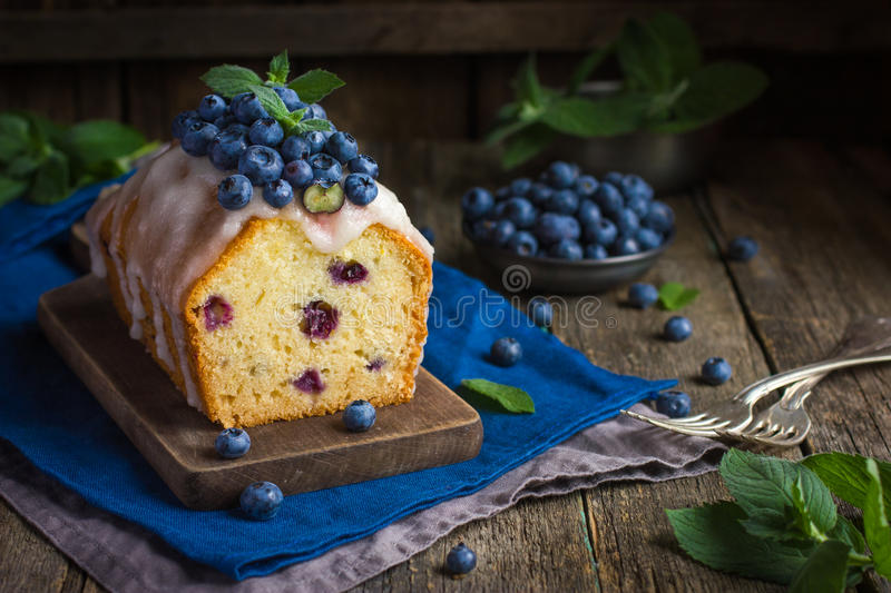 Blueberry cake with sugar icing and fresh berries. On rustic background royalty free stock photography