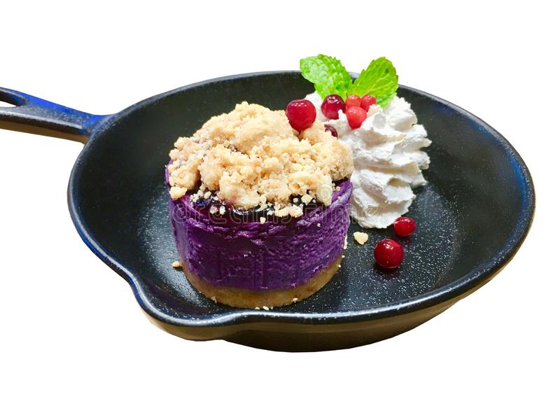 Blueberry cheesecake with whipped cream and cracker, cranberry and peppermint decorate inside classic black pan crockery stock image