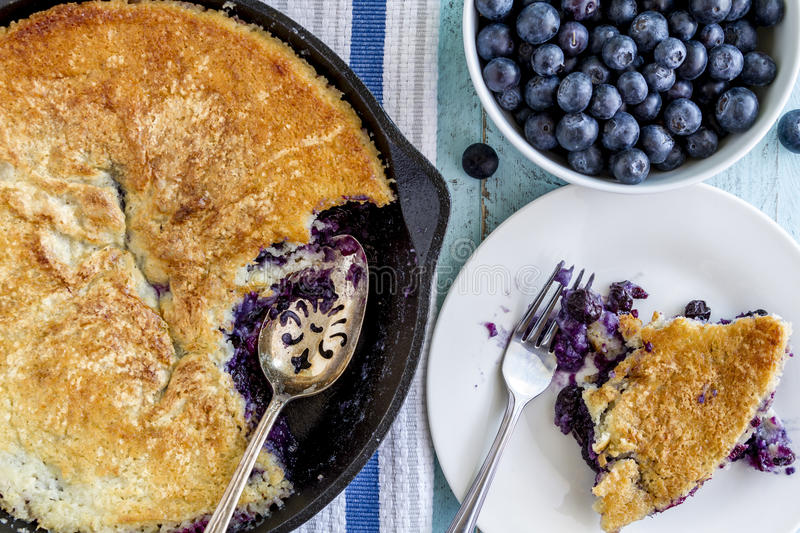 Blueberry Cobbler Baked in Cast Iron Skillet. Homemade fresh blueberry cobbler baked in cast iron skillet pan with piece on white plate and bowl of blueberries stock images