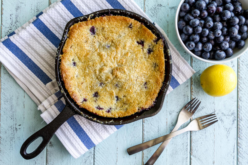 Blueberry Cobbler Baked in Cast Iron Skillet. Homemade fresh blueberry cobbler baked in cast iron skillet pan with piece on white plate and with bowl of royalty free stock photos