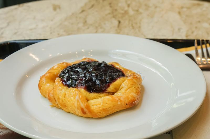 Blueberry danish on white ceramic plate for breakfast. Close up blueberry danish on white ceramic plate for breakfast royalty free stock photography