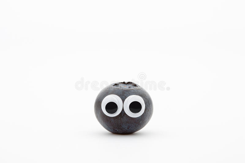 Blueberry with googly eyes on white background. Blueberry face royalty free stock photos