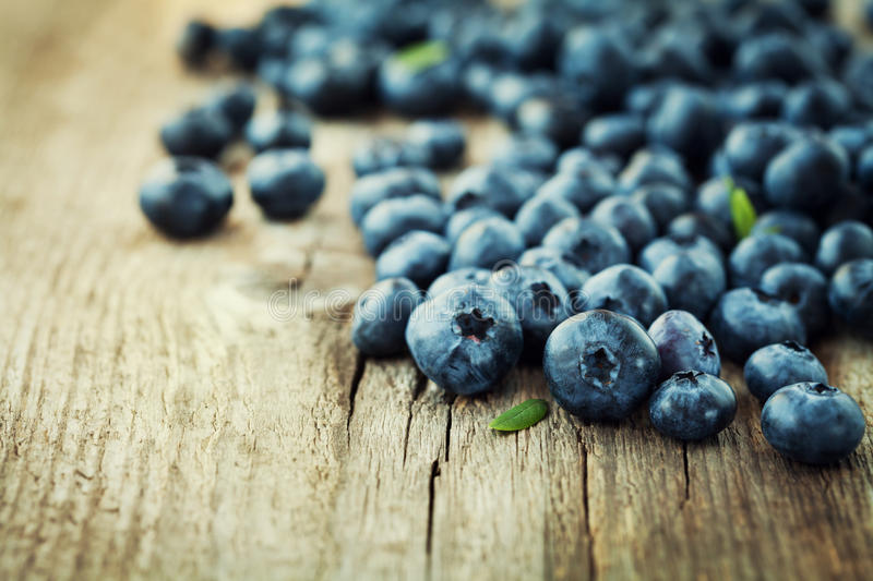 Blueberry, great bilberry or bog whortleberry on wooden board royalty free stock images