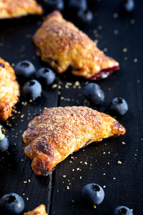 Blueberry hand pies on black wooden table. A delicious dessert of puff pastry and organic blueberries on black background stock photography