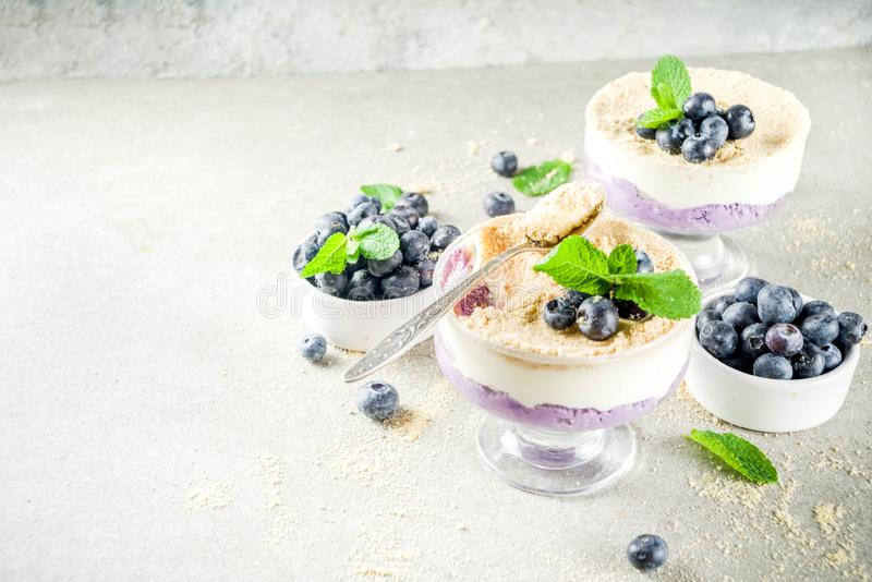 Blueberry inverted cheesecake. Sweet summer dessert, Blueberry no baked inverted cheesecake in glass, grey stone background copy space stock photo
