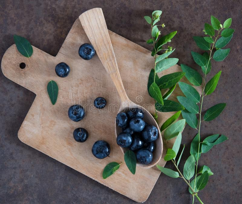 Blueberry and mint, wooden spoon and board top view royalty free stock photos