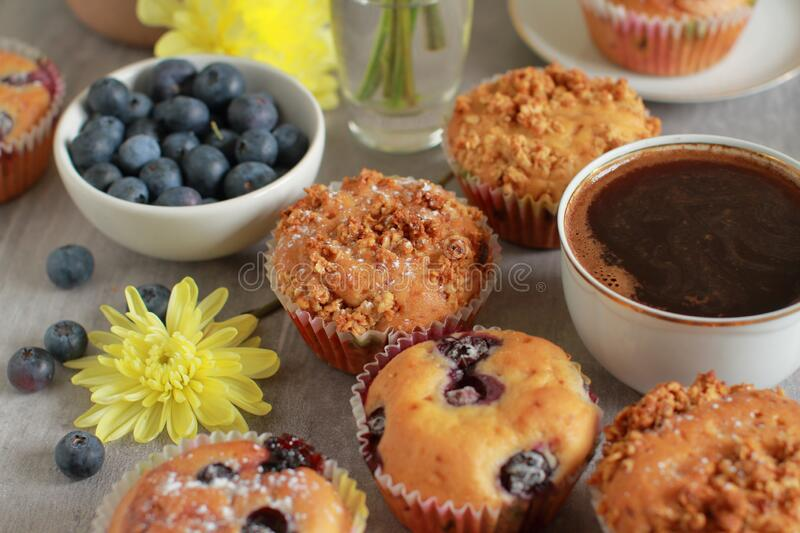 Homemade blueberry muffins on a rustic  table and a cup of coffee stock image