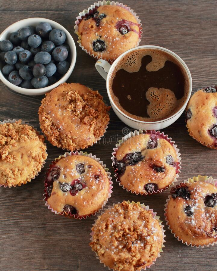 Blueberry muffins on a rustic wooden table and a cup of coffee royalty free stock photos