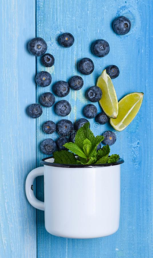 Blueberry on mug spill blue background top view mint lime rustic summer. Berries royalty free stock image