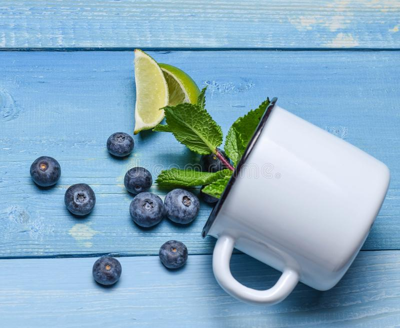 Blueberry on mug spill blue background top view mint lime rustic summer. Berries royalty free stock photo