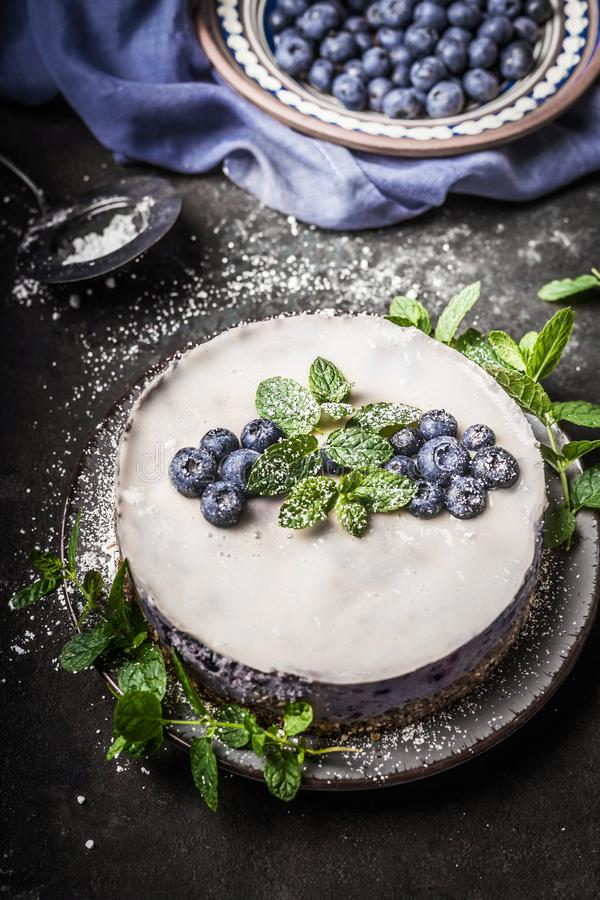 Blueberry no bake vegan cheesecake with coconut milk , decorated with fresh blueberries and mint leaves on dark rustic background stock image