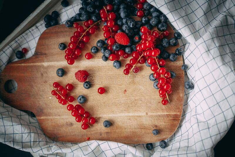 Blueberry raspberry and red currant on the wooden board royalty free stock image