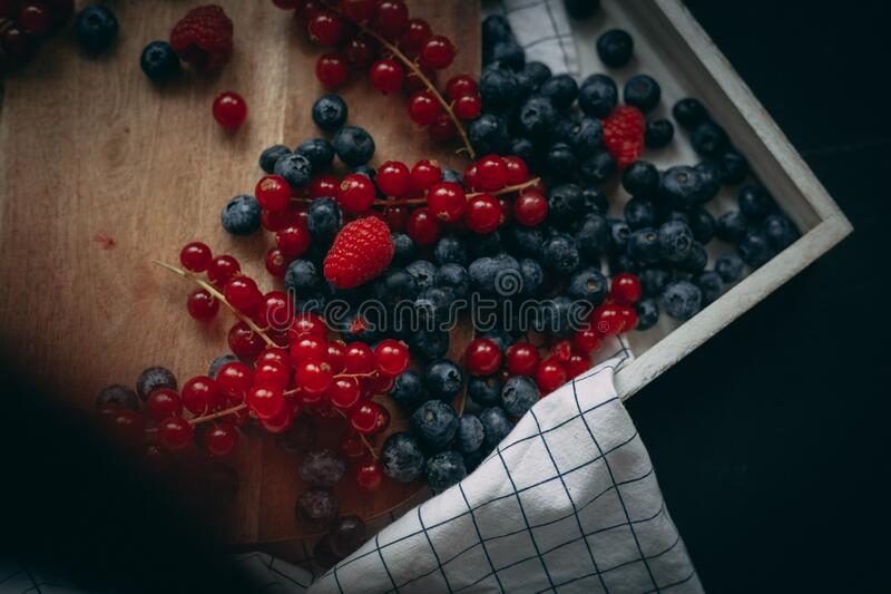 Blueberry raspberry and red currant on the wooden board royalty free stock photo