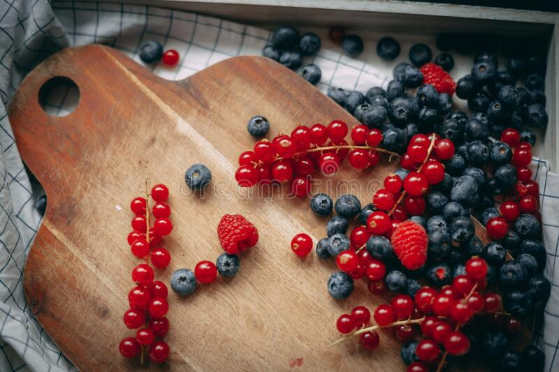 Blueberry raspberry and red currant on the wooden board royalty free stock photography