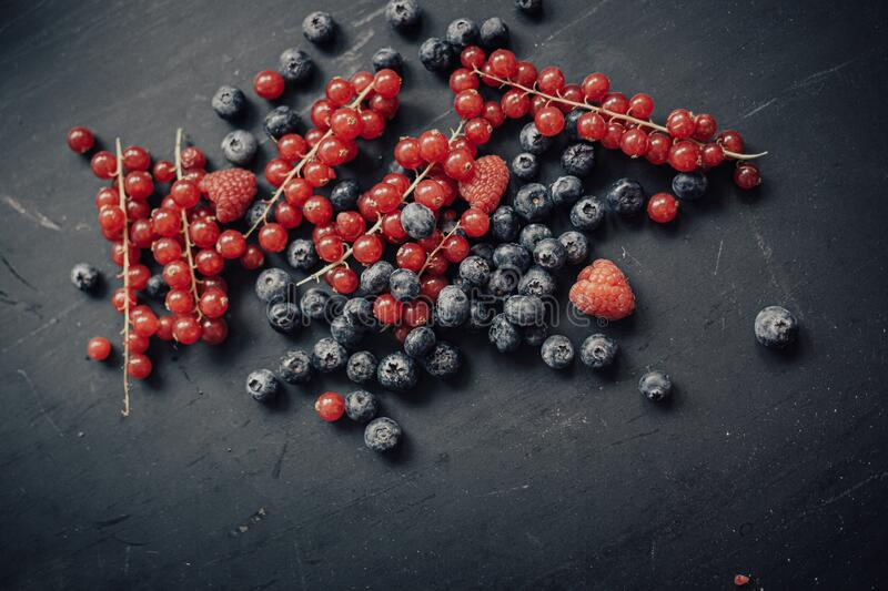 Blueberry raspberry and red currant on the wooden board royalty free stock images