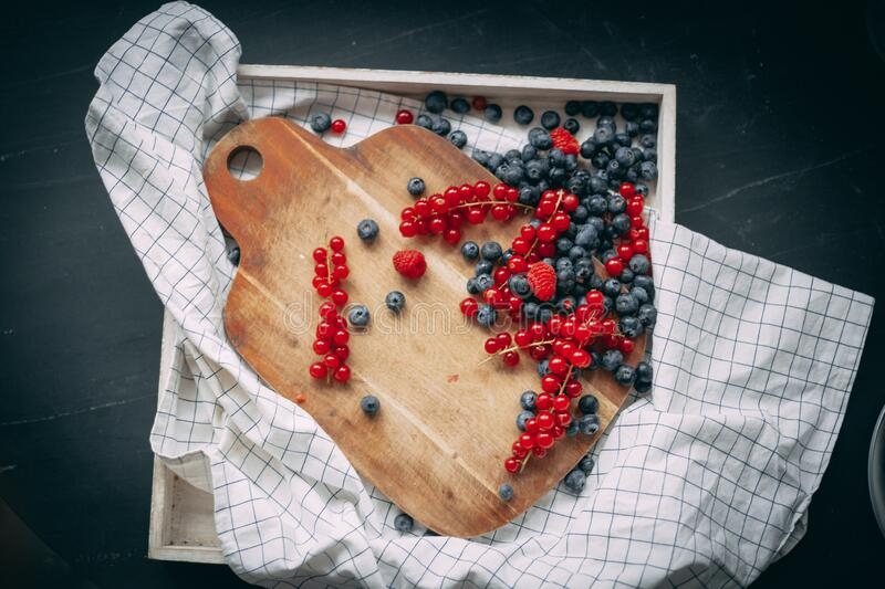 Blueberry raspberry and red currant on the wooden board royalty free stock photos