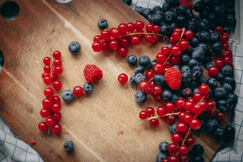 Blueberry red currant raspberry on the wooden board stock image