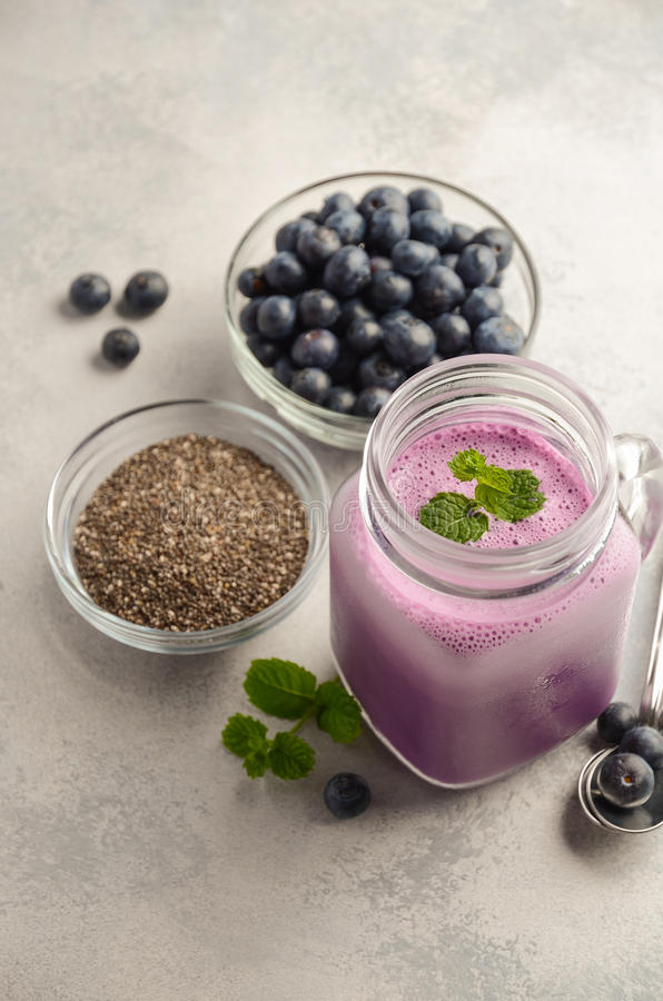 Blueberry smoothie with chia seeds in glass jar on grey concrete background royalty free stock images
