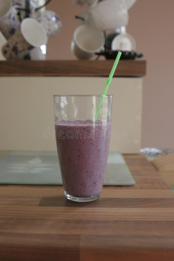 Blueberry smoothie in glass with straw. A healthy fresh blueberry smoothie in a tall glass with a green straw taken in a kitchen during daylight royalty free stock photo