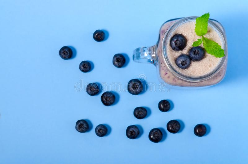 Blueberry smoothie with mint in mason jar glass with berries and mint. Above view on blue table. Healthy food stock images