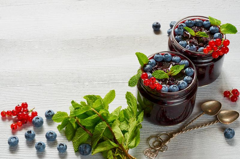 Blueberry smoothies with fresh mint, red currant and vintage spoons on the gray background close up. Summer detox superfoods. Breakfast or cold healthy dessert royalty free stock photos