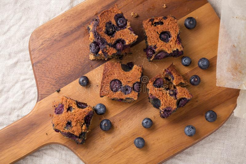 Blueberry square bars on wooden board. With blueberries, top view royalty free stock photography