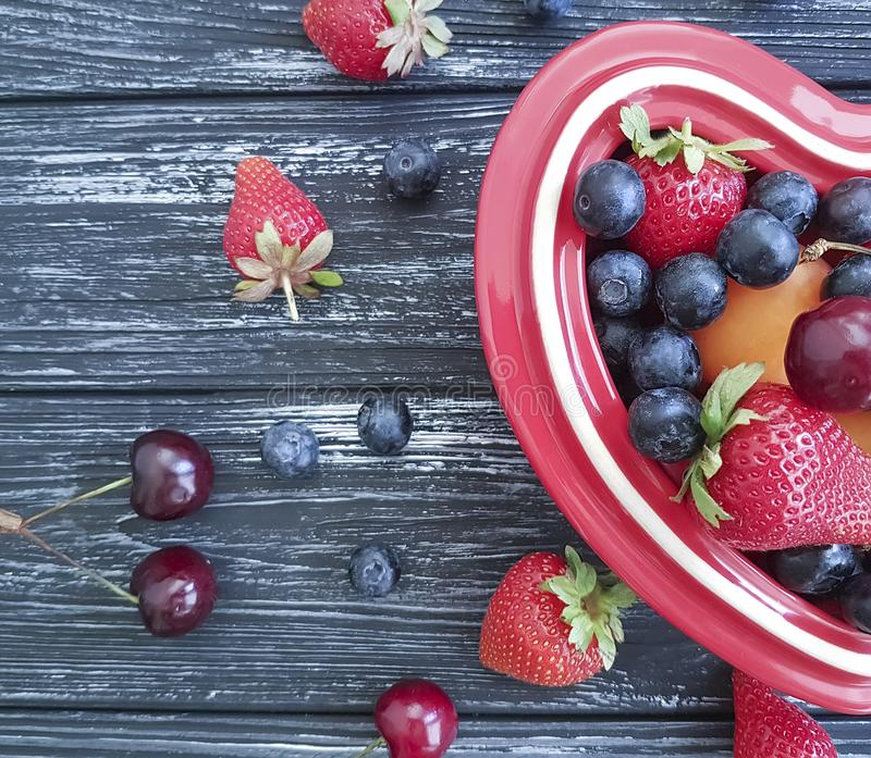 Blueberry, strawberry cherry seasonal healthy plate heart on old black wooden royalty free stock photos