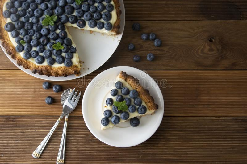 Blueberry Tart. Homemade piece of berry tart, cake with cream. Fresh sweet dessert with fruit. Top view. wooden, rustic background royalty free stock images