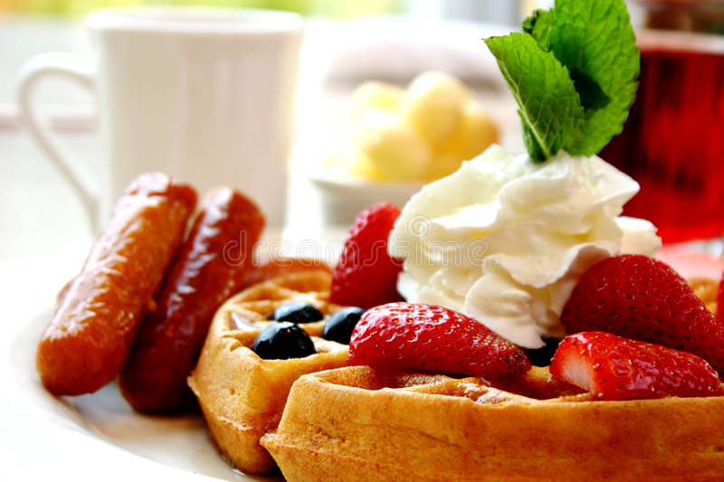 Blueberry waffles with strawberries and sausages. Blueberry waffles with maple syrup, topped with whipped cream and mint leaf. Served with fresh strawberries and royalty free stock images