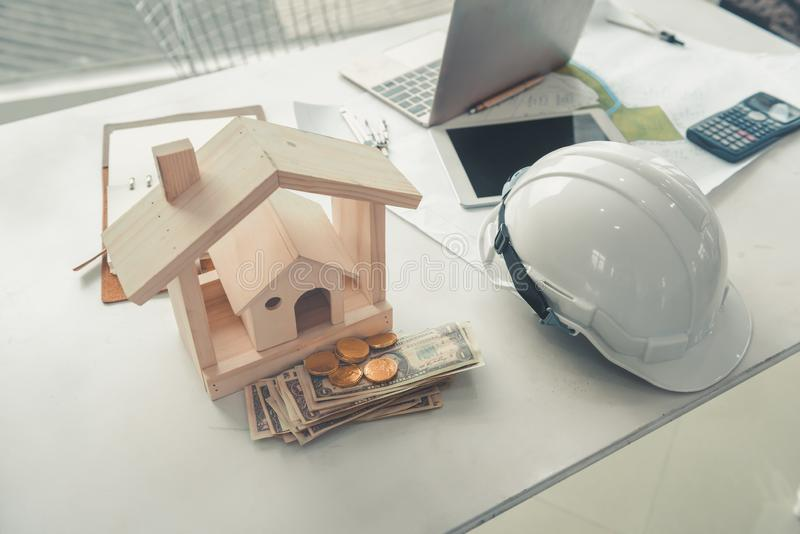 Blueprint of construction engineers or architects and wooden modeling house on a tabletop., Workspace layout of professional stock photography