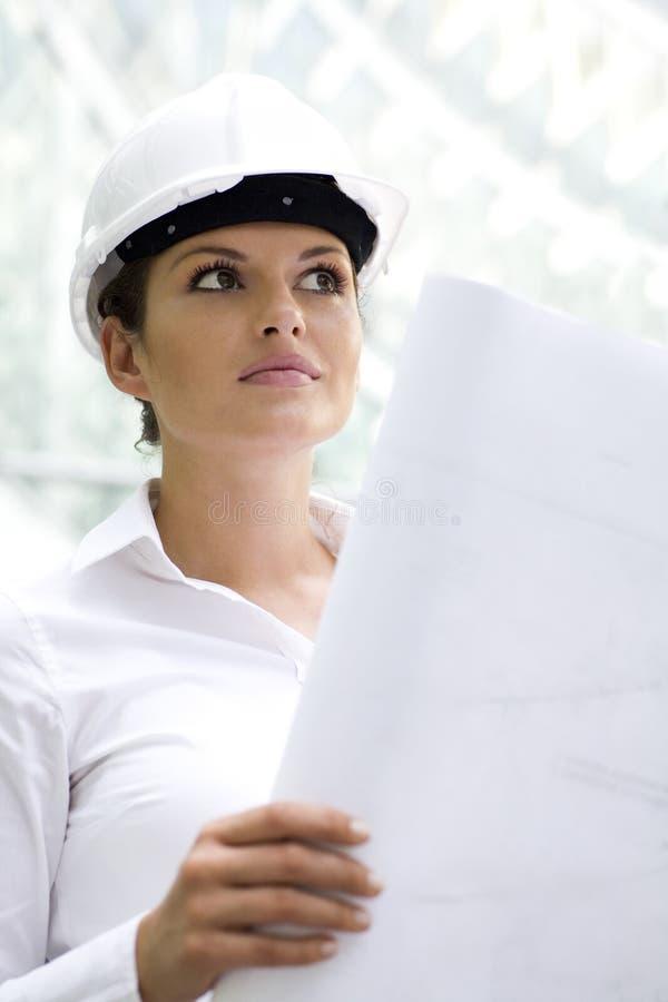 blueprints женщина удерживания hardhat стоковое изображение