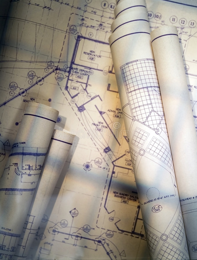 Blueprints. Rolled and unrolled illuminated with window light royalty free stock images