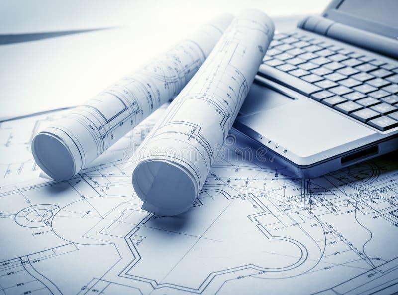 Blueprints rolls and laptop stock photo