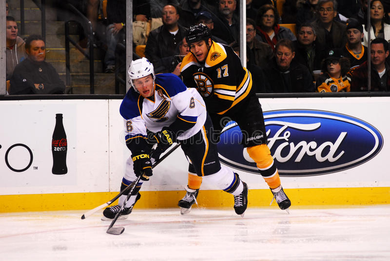 Blues Defenseman Erik Johnson. St. Louis Blues Defenseman Erik Johnson clears the puck away from Bruins forward Milan Lucic and gets it out the Blues zone royalty free stock images