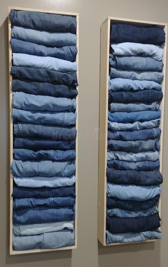 Blues-jean empilées comme décoration de mur images stock