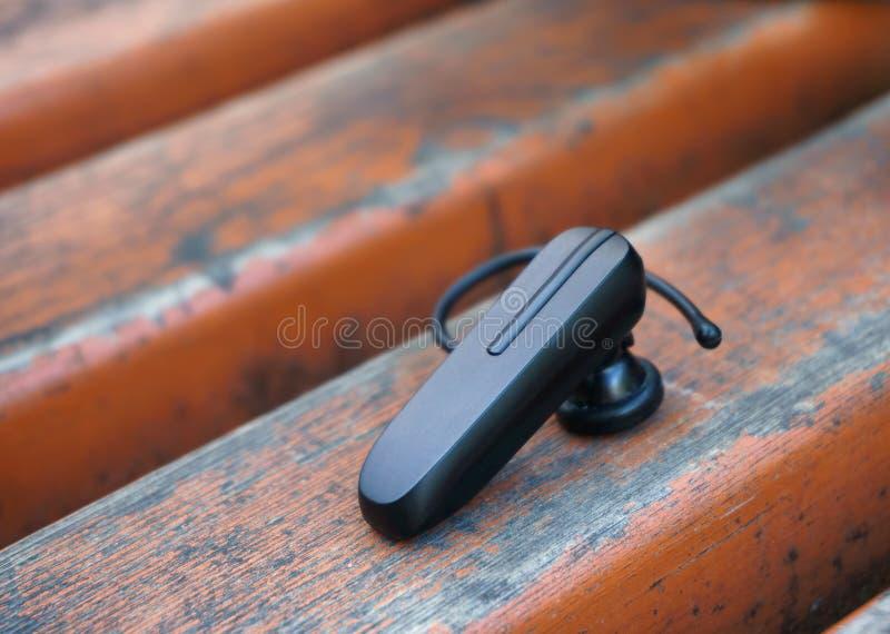 Bluetooth słuchawki lying on the beach na ławce obraz stock
