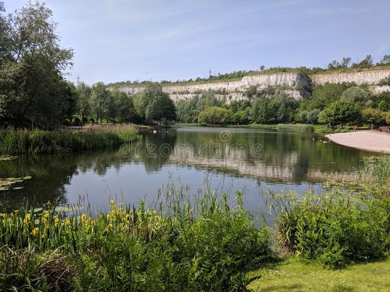 Bluewater Lake scene. Lake and greenery cliffs trees pebbles shore high lily pads grass UK spring midday royalty free stock image