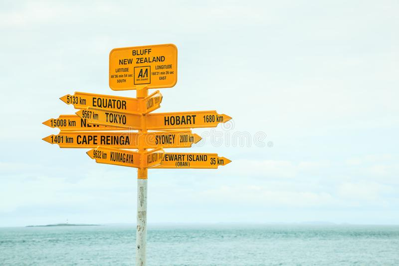 Bluff New Zealand yellow Signpost, with arrows pointing to different directions, major destinations, big cities such as Tokyo. Sydney, New York, Hobart stock image