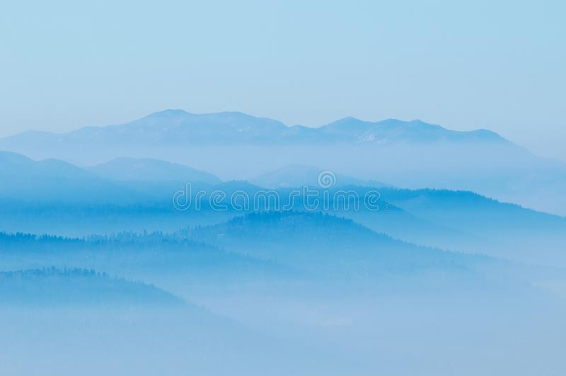 Hills with rising fog from the valleys below stock photos
