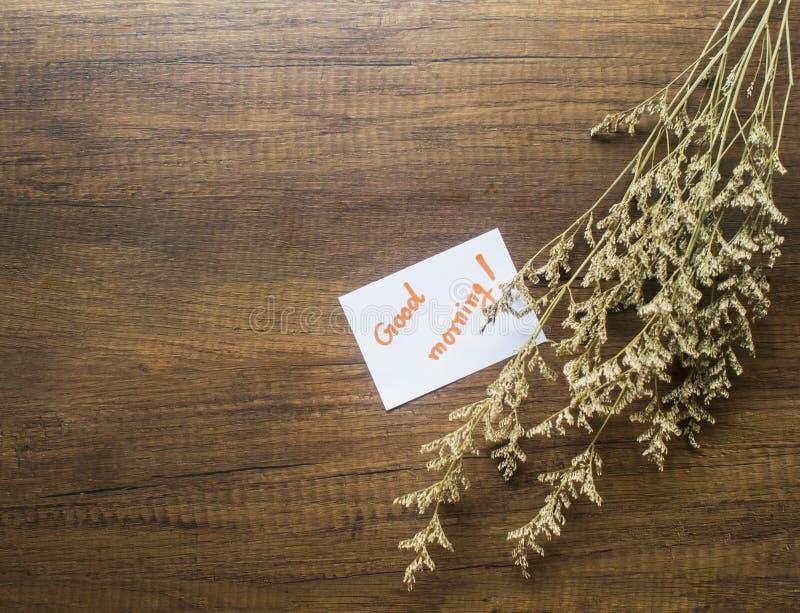 Blume und Blatt Papier mit Text u. x22; gutes morning& x22; auf der Holztischnahaufnahme lizenzfreie stockbilder