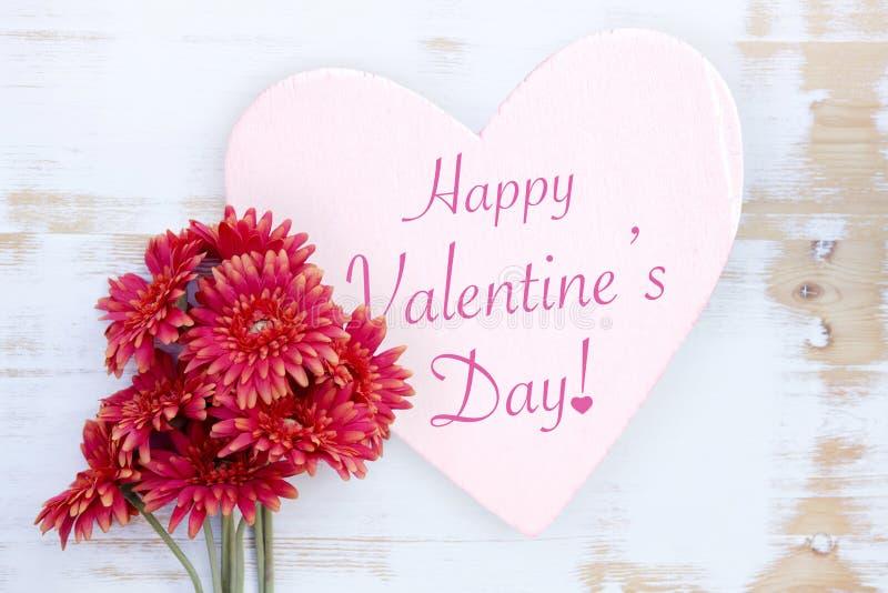 Blumen auf Holztisch mit Wörter glücklichem Valentinsgruß-Tag lizenzfreie stockbilder