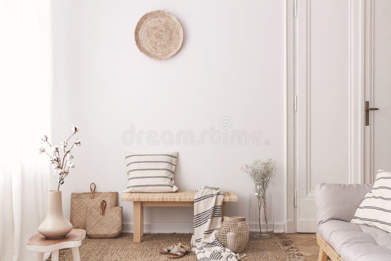 Blumen auf Holztisch nahe Bank mit Kissen und Decke im weißen Wohnzimmerinnenraum Reales Foto stockfoto