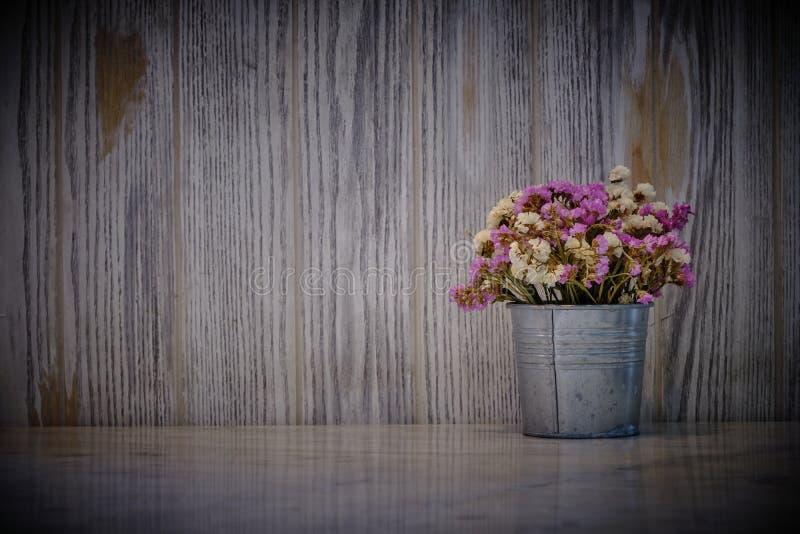 Blumen auf Topf mit leerer Marmortabelle auf dunkler alter hölzerner Wandbeschaffenheit mit natürlichem Musterhintergrund stockfotografie