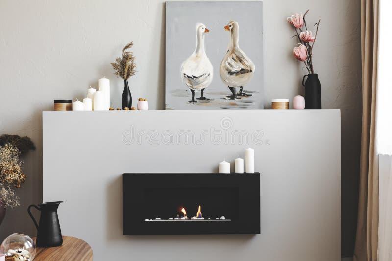 Blumen in den Vasen, in den Kerzen und in der rustikalen Malerei auf Regal über eco Kamin im modernen Wohnzimmerinnenraum stockfoto