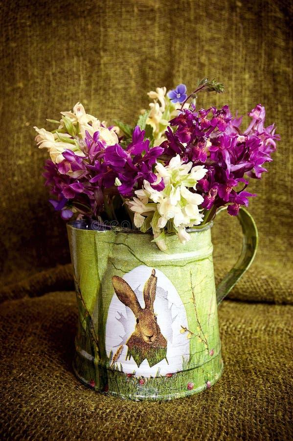Blumen in der Metallbauchigen weinflasche verziert mit Illustration des Osterhasen- und Ostereies auf der grünen Aufbauschung stockfoto