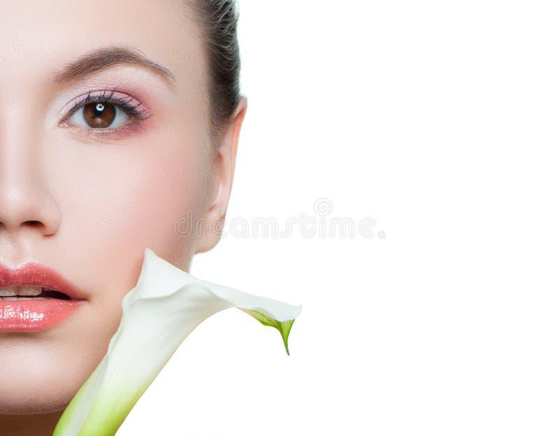 Blumen der weißen Lilie und Gesichtsnahaufnahme der jungen Frau lokalisiert auf weißem Hintergrund stockfotos