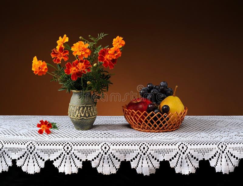 Blumen in einem keramischen Vase und in einer Frucht lizenzfreie stockfotos
