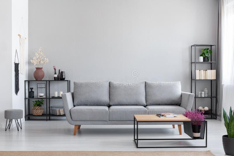 Blumen im Holztisch vor grauem Sofa in der modernen einfachen Wohnung Innen mit Schemel stockfotografie
