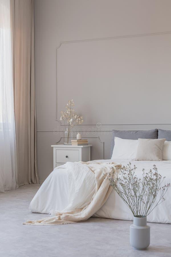 Blumen im Vase auf dem Boden des einfachen Schlafzimmers mit grauer Wand und weißen Möbeln, Kopienraum auf leerer Wand stockfotografie